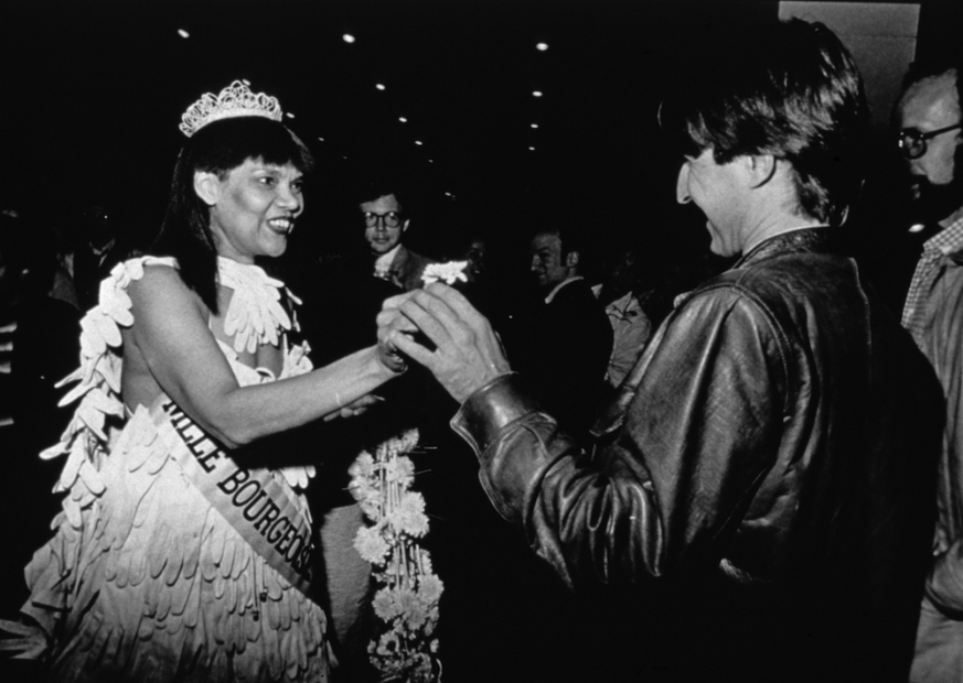 A black-and-white photograph of a Black woman in a beauty pageant gown, crown, gloves, bouquet, and sash extending appearing to hand a small flower to a light-skinned man in a leather jacket.