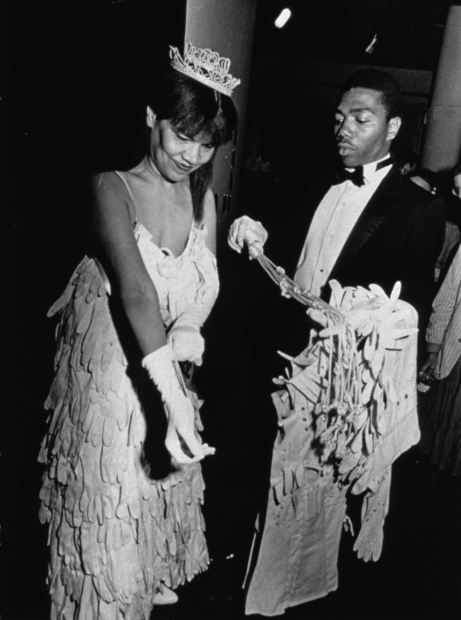 A black-and-white photograph of a Black woman in a beauty pageant gown and crown adjusting her gloves as a young Black man in a tuxedo holds her coat, bouquet, and sash.