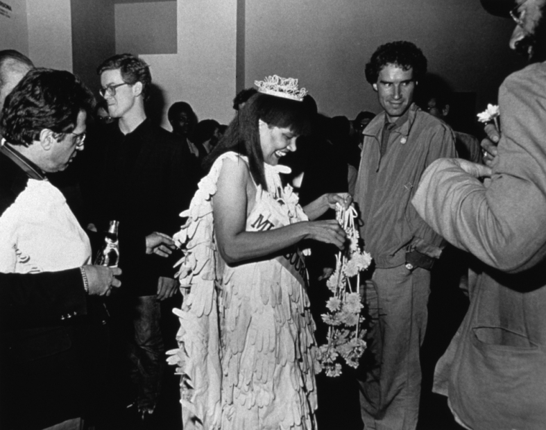 A black-and-white photograph of a Black woman in a beauty pageant gown, crown, gloves, bouquet, and sash standing in the center of a crowd,adjusting her bouquet while smiling and, looking down.