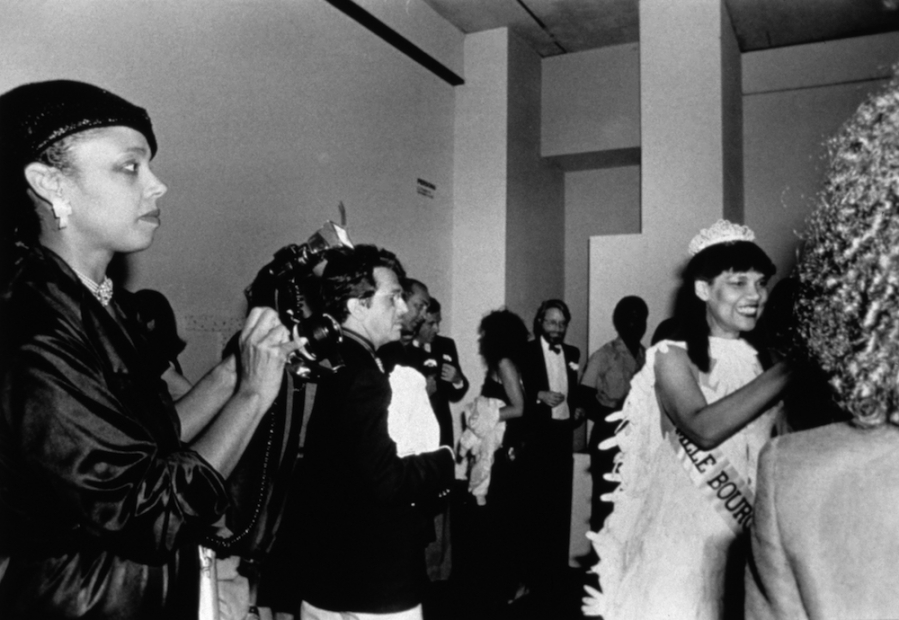 A black-and-white photograph shows a Black woman in a beauty pageant gown, crown, gloves, bouquet, and sash in the bottom right corner of the image greeting a stranger as others wait to greet and photograph her.