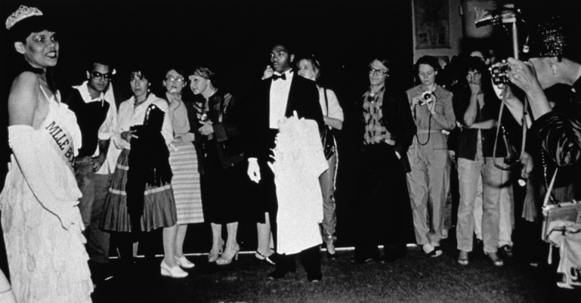 A black-and-white photograph shows a Black woman in a beauty pageant gown, crown, and gloves at the left being watched by a line of less formally dressed people. A young Black man in a tuxedo stands at attention in the center of the frame, holding a white coat, and a photographer shoots the scene from the far right.