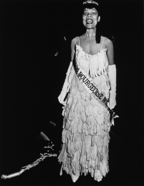 A black-and-white photograph of a Black woman in a beauty pageant gown, crown, gloves, and sash standing in a dark gallery room facing the viewer with her mouth wide open in mid-speech.