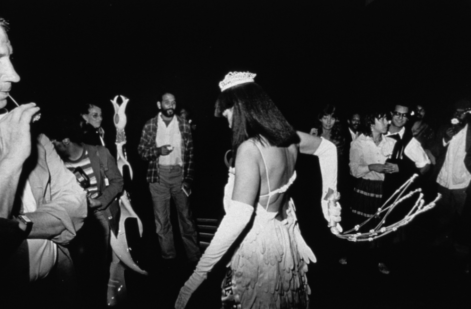 A black-and-white photograph of shows a Black woman in a beauty pageant gown, crown, and gloves whipping a white cat o' nine tails behind her in a crowded gallery.