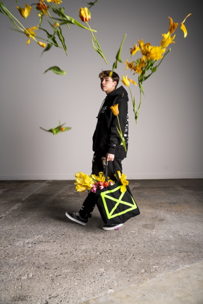 A young man dressed all in black walks looks toward the camera mid-stride as yellow tulips fly toward him.
