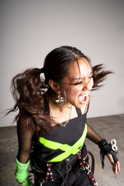 A young woman with black pigtails and medium skin wearing a black top with a large bright green X, gloves, and chains is captured mid-scream.