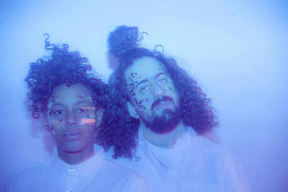 The two members of Optic Bloom with stars on their faces in a blue colored photograph.