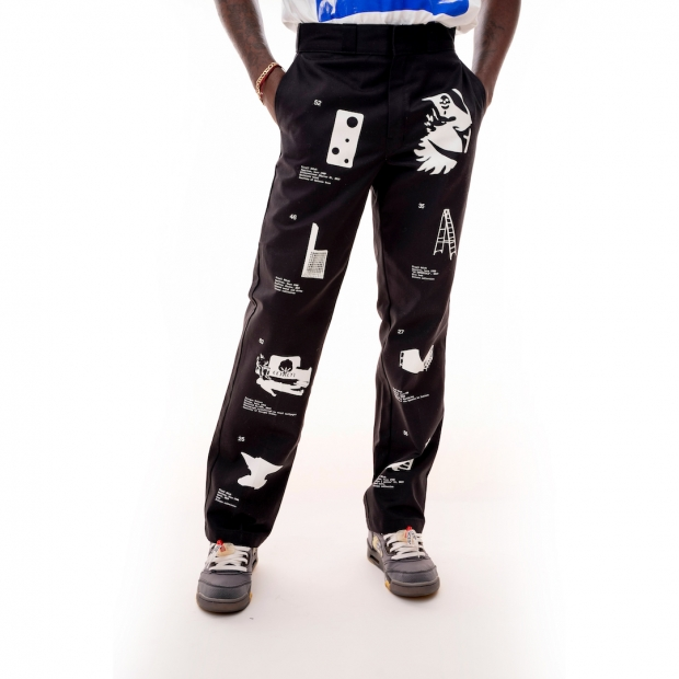 Loose black pants with four white images of artworks printed down the length of each leg, worn by a dark skinned model.