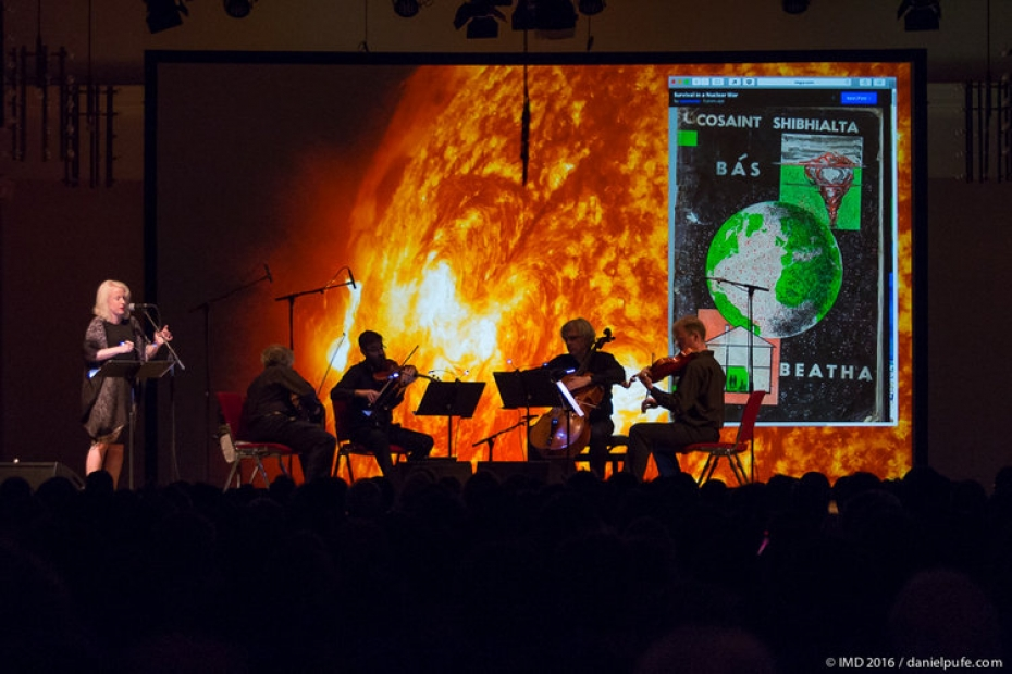 A seated string quartet and a standing person in front of a projected image of fire.