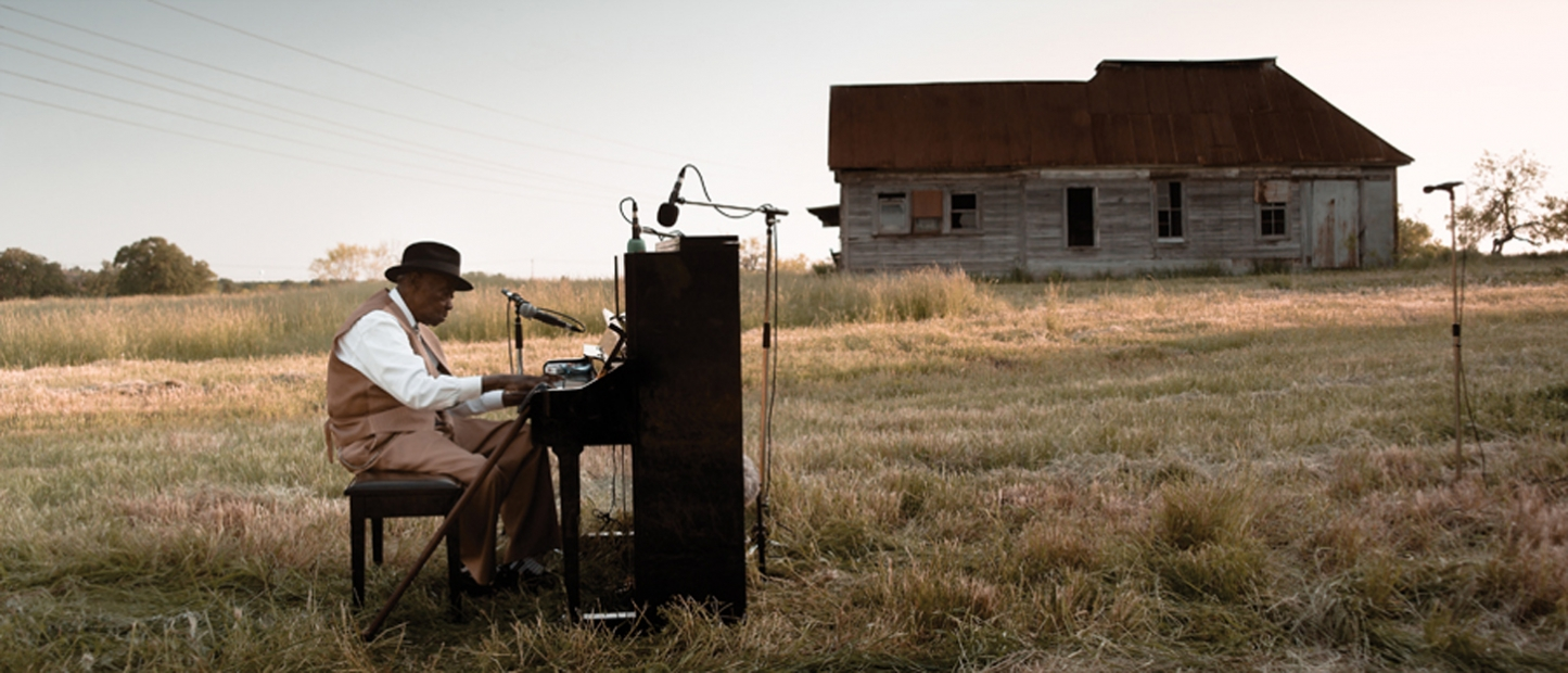 A video still shows musician Pinetop Perkins, an older Black man, playing an upright piano in an open field before a wooden house.