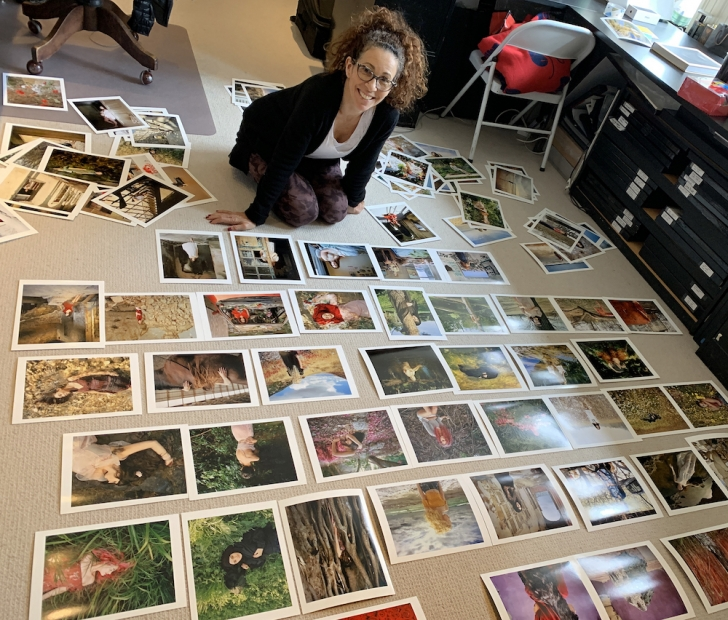 A woman kneels in an art studio amid dozens of photographs laid out on the floor. She is wearing yoga pants, a white shirt, and a cardigan, and smiling at the camera.
