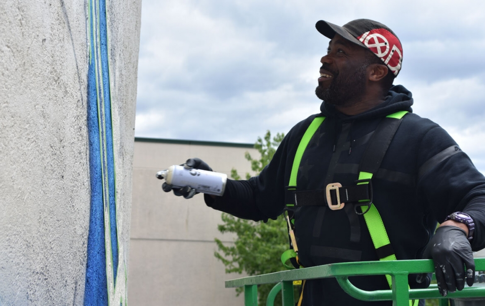 A man wearing a harness stands in a lift and spraypaints a wall