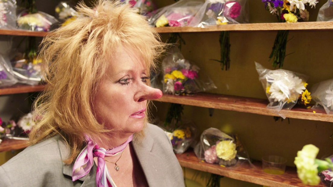 A film still shows a white woman with a jacket, neck scarf, a messy blond mullet, and unkempt blond hair and an enlarged red-tipped nose sitting in a room of flower arrangements on shelves.