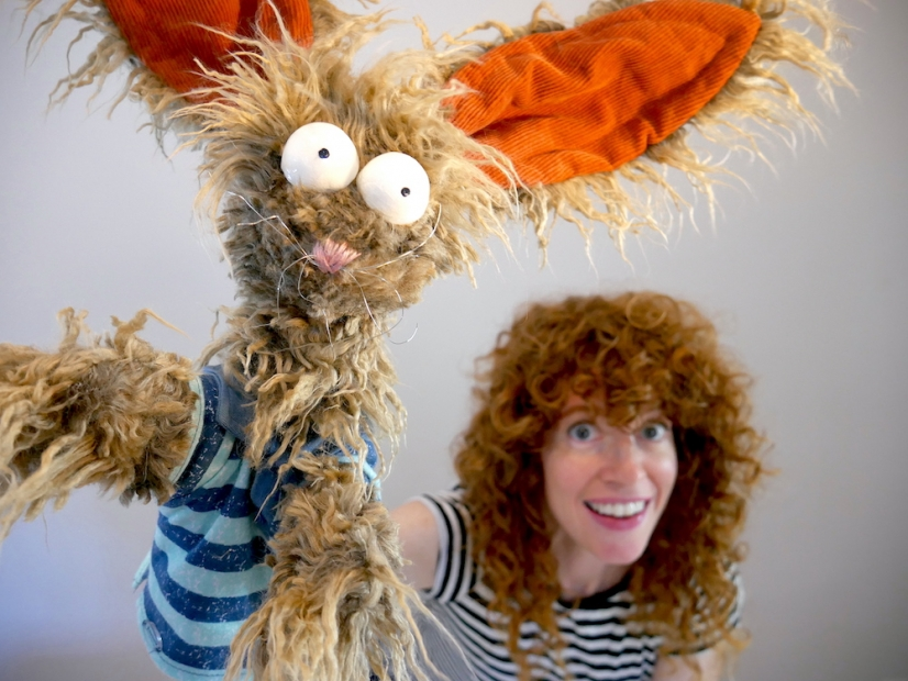 Smiling light-skinned woman holds up a brown rabbit puppet at the viewer.