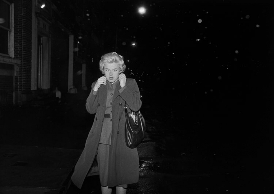 A black-and-white photograph of the artist on a very dark urban street, with blond hair and a dress skirt and blouse under a trench coat that she pulls closed around her neck.