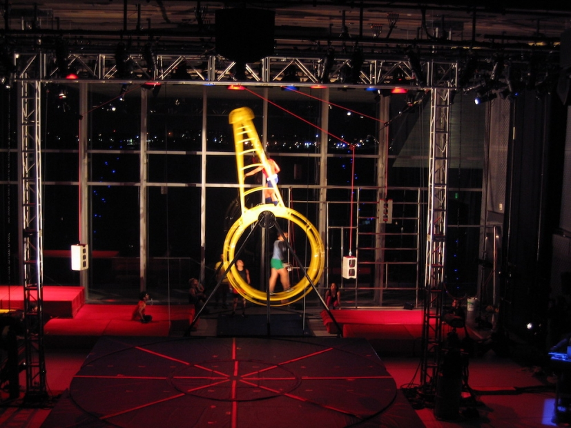 A slightly blurry photo shows several dancers inside and on top of a yellow human-sized hamster wheel on a stage full of scaffolding.