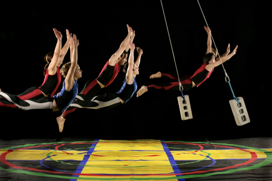Five dancers seem to fly several feet off a colorful stage floor while two cinderblocks suspended on wires swing among them.