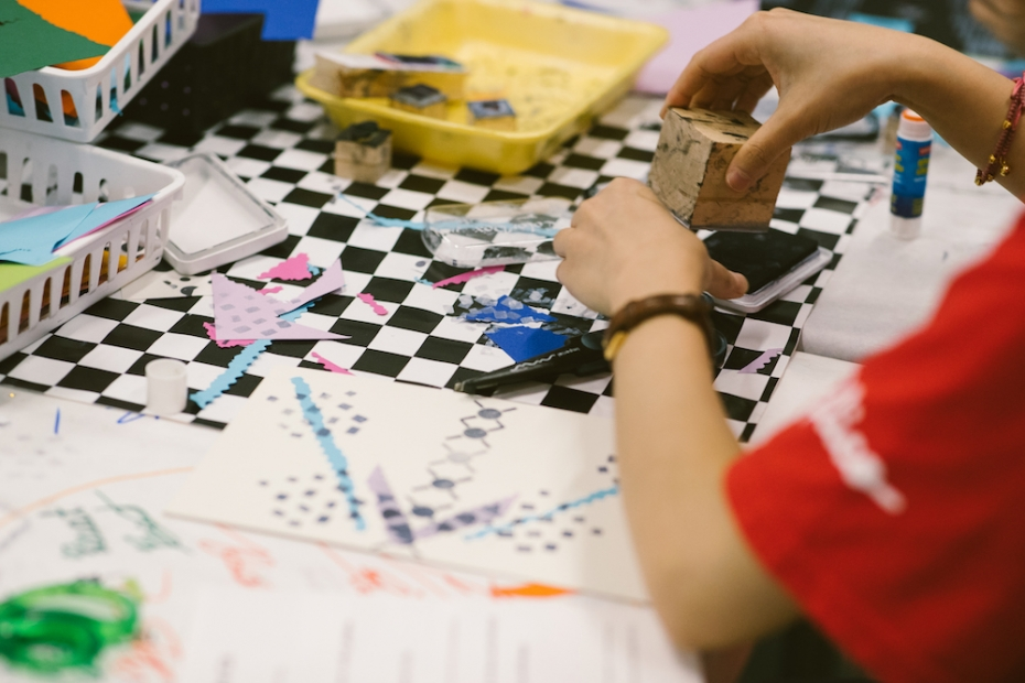 An art-making table full of art supplies, and a youth creating a stamp