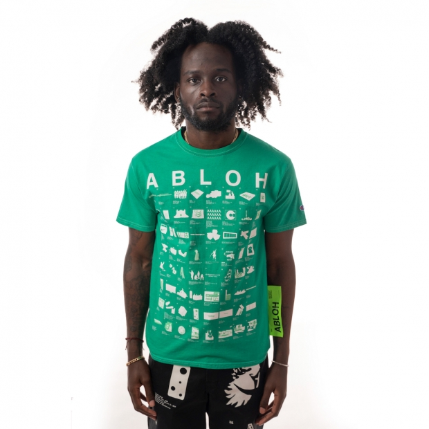 Front view of bright green shirt with rows of artworks in simplified white print and a large yellow-green tag attached to the side, worn by dark skinned model.