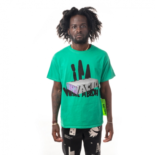 """Front view of bright green shirt with graffitied white block slightly obscuring thick graffiti-like black text saying """"ICA"""" and """"Virgil Abloh"""", worn by a dark skinned model."""