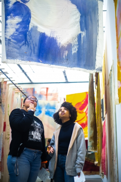 Two teens looking at the unstretched paintings hung in Vivian Suter's immersive installation.