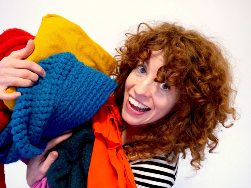 A woman with curly red hair smiling at the camera with piles of knits and fabrics in her arms.