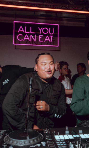 """DJ Yung Towfu in front of a neon sign reading """"all you can eat."""""""