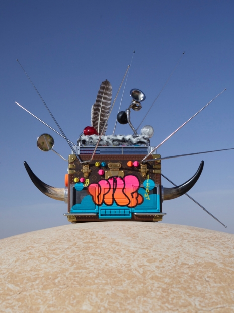 A repurposed guitar amp sits atop a dry, desert-like surface, and is adorned with spikes, animal horns, feather, and other metallic objects with a colorful spray paint on the front surface.