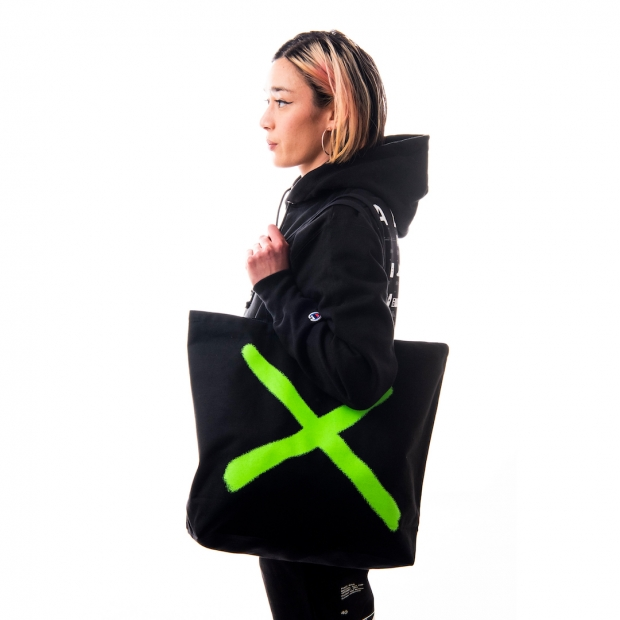 Profile view of light-medium skinned model holding a black tote bag with a large neon green X.