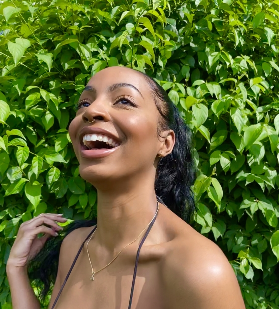 A medium dark-skinned women smiling and looking up with greenery in the background.
