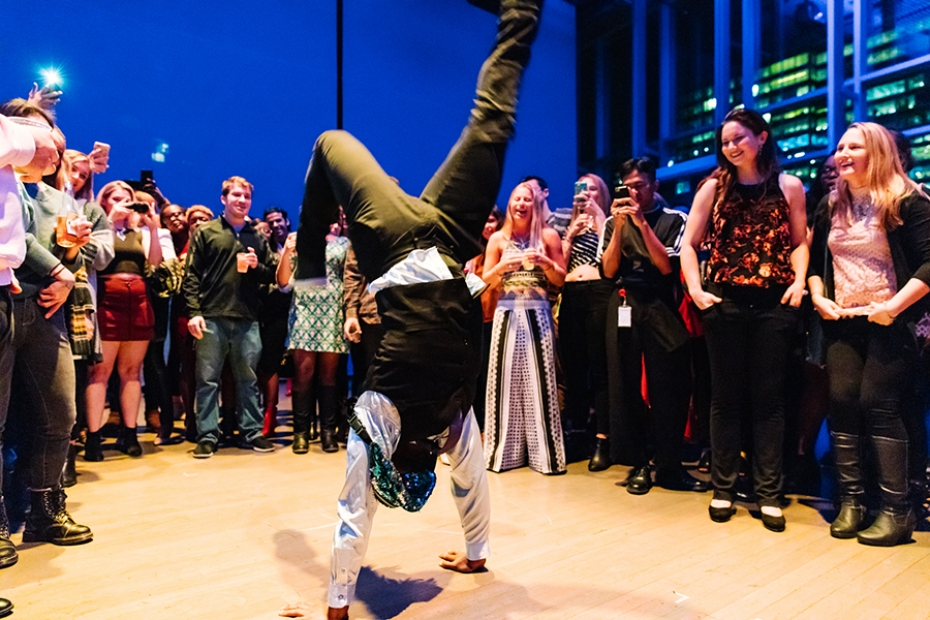 A person breakdancing in the ICA theater with people watching.