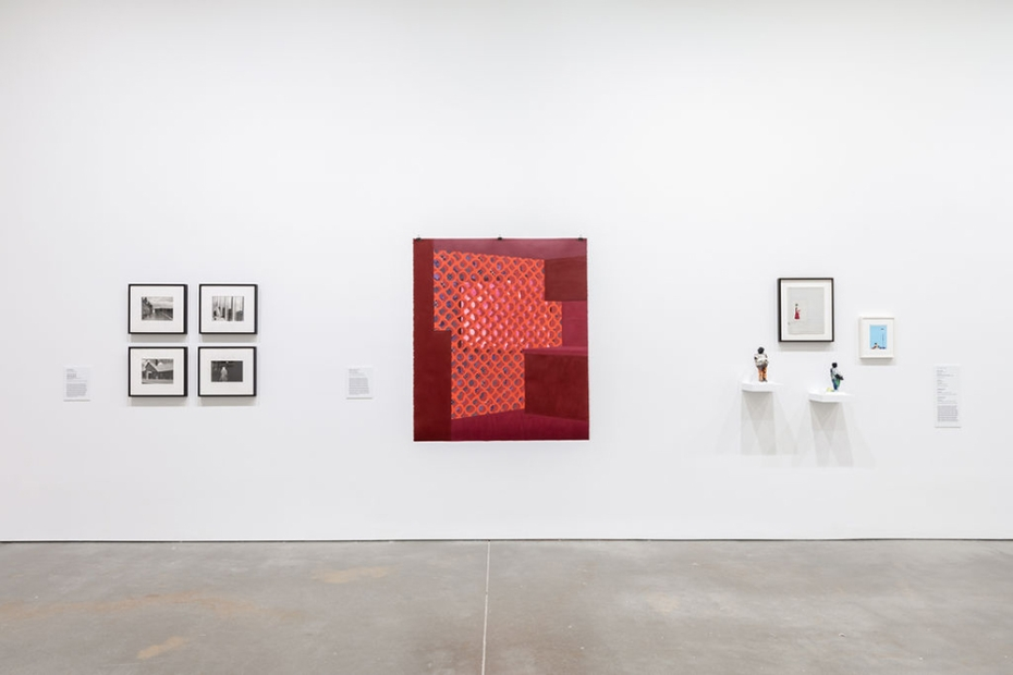 A wall with a red, unframed painting in the middle showing a lighter red woven mesh. To the left, four framed black and white photos hang in a grid. On the right, two small sculpted figures sit on short shelves. Two small framed works hang above them.