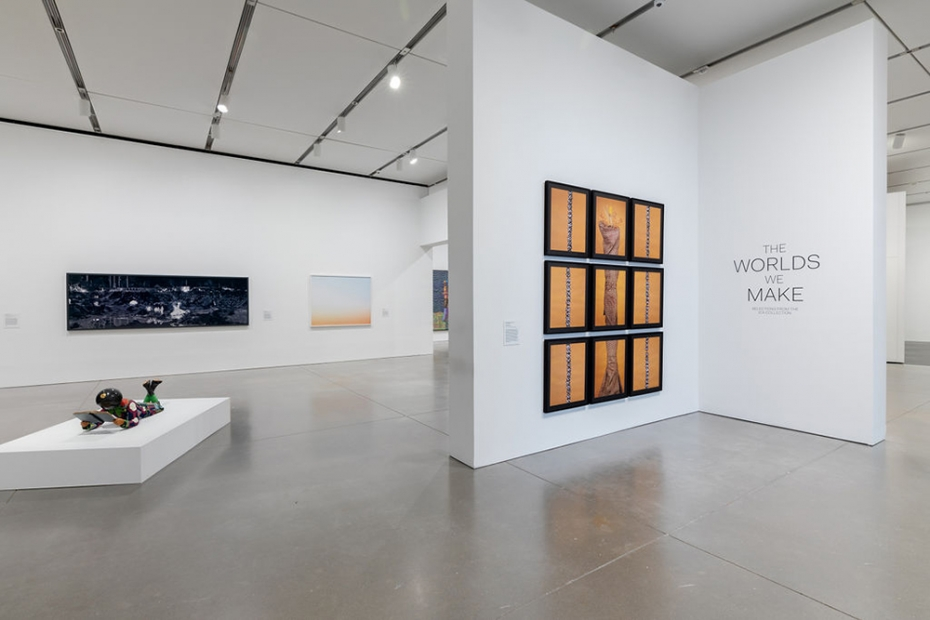 """Installation view of gallery with a wall showing sign: """"The Worlds We Make"""". Several photographic works hang on the walls and there is a multicolored sculpture of a figure reading on the floor."""
