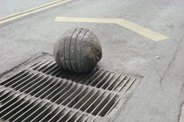 A color photograph of a large, grey plasticine sphere on a dirty grate in the middle of a paved street. The sphere shows indentations from the grate.