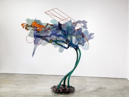 A large-scale, colorful sculpture of bronze and steel resembling a tree or flower.