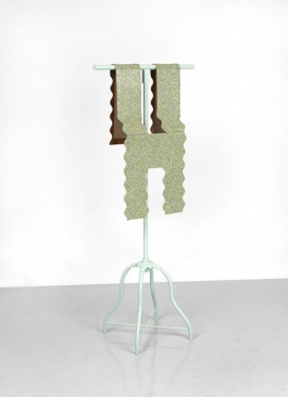 A sculpture of a scalloped form of speckled gold and green linoleum resembling a vest, draped over a dressmaker's work stand.