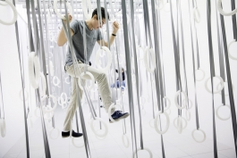 Man experiencing William Forsythe's The Fact of Matter by climbing through suspended rings