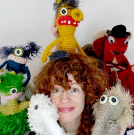 A red-headed woman surrounded by stuff dolls.