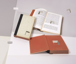 A color photograph depicts two open books and one closed book with illusionistic square holes painted on their surfaces and laid on top of creased paper supports to appear as though a still life in a flat or two-dimensional plane.