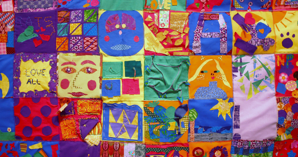 A sewn tapestry with various and colorful quilt squares.