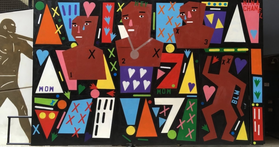 A wall-size work features colorful cutout figures, hearts, Xs, and other dynamic shapes.