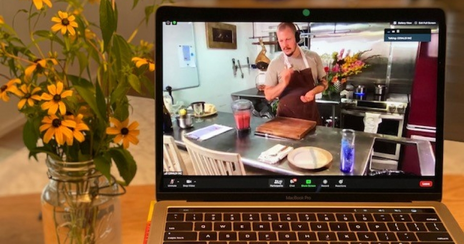 A laptop showing a chef in a profession kitchen sits next to a jar of cut flowers.