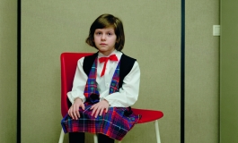 A color photograph of a young light-skinned girl with short brown hair in a blouse, vest, plaid skirt, and dress shoes sitting on a red chair with her feet not touching the ground, positioned at an angle and gazing at the viewer.