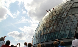 A crowd of onlookers watch from the ground-level street as three performers walk down London City Hall, a spherical glass building.