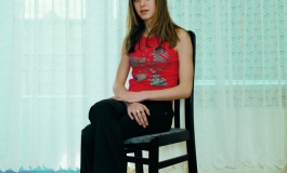 A color photograph of an light-skinned adolescent girl with long brown hair wearing a red tank and black pants sitting on a chair, positioned at an angle and gazing at the viewer.
