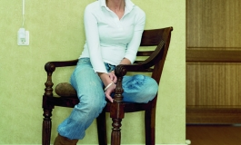 A color photograph of a light-skinned young woman wearing a white blouse and blue jeans, sitting sideways on a chair to face the viewer.