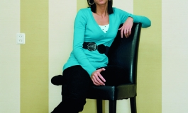 A color photograph of a light-skinned young woman with shoulder-length brown hair wearing a turquoise blouse and sitting with one arm slung over the back of a black chair, positioned at an angle and gazing at the viewer.