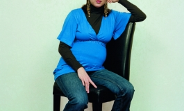A color photograph of a pregnant light-skinned woman wearing a bright blue blouse and sitting with one arm propped on the back of a black chair, positioned at an angle and gazing at the viewer.