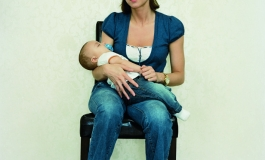 A color photograph of a light-skinned woman with short brown hair in a dark top, jeans, and white socks sitting in a chair with a baby in her arms, facing and gazing at the viewer.