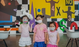 Three children wearing colorful masks and standing in front of the art wall.