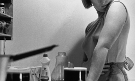 A black-and-white photograph of the artist posing in a small, cramped kitchen, looking over her shoulder. She wears a sleeveless top and dramatic eye makeup and the image is cropped to include dishes and dish detergent but cut off the top of her head.